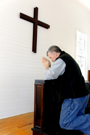 Man praying and kneeling in front of a simple wooden cross at a church. photo