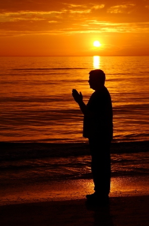 Man praying at the ocean at sunset with the sun and light above him. Stock Photo - 17565708