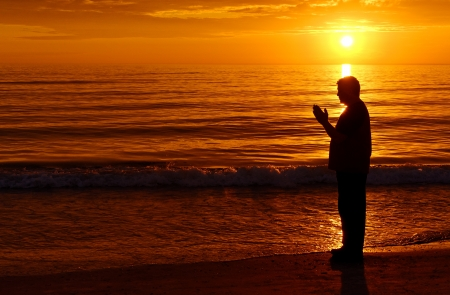 hope: Man standing and praying at the ocean with orange sunset in background Stock Photo