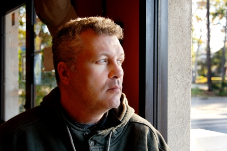 aged: Middle aged man sitting by a window in a restaurant