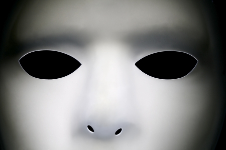 White alien looking face with big black eyes.