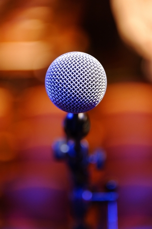 Single microphone against a peach colored background. Stock Photo