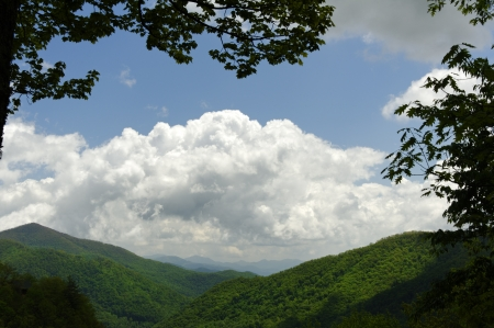 laden: Puffy white clouds above forest laden mountains. Stock Photo