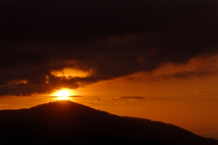 Dramatic sunrise with dark storm clouds on the top of a mountain.