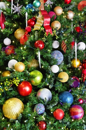 Many different colored bulbs on a Christmas tree.