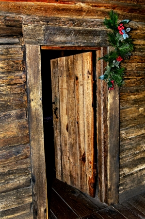 An inviting open cabin door at Christmas time. Stock Photo