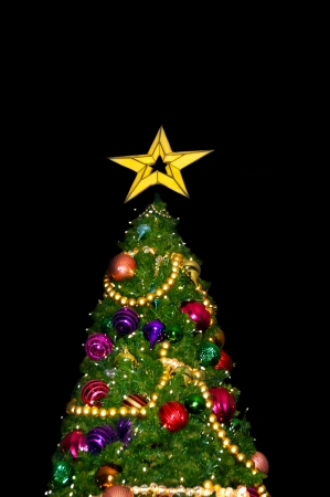 A green Christmas tree with a bright gold star and beautiful decorations.