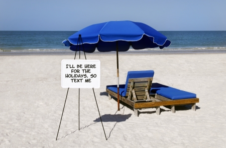 Blue umbrellas and beach chairs with a whiteboard that says, Ill be here for the holidays, so text me.