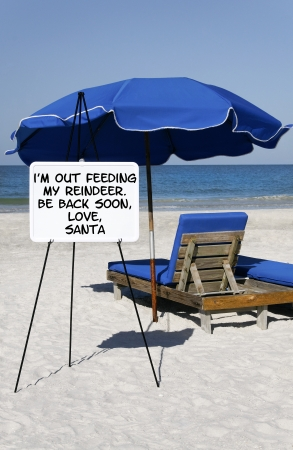 A sign at the ocean that says, Im Out Feeding My Reindeer.  Be Back Soon, Love Santa in front of a blue umbrella and beach chair. Stock Photo