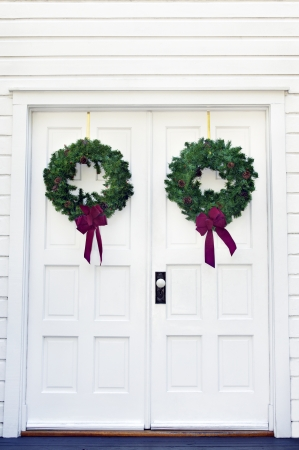Two green Christmas wreaths with red ribbons on a white door.
