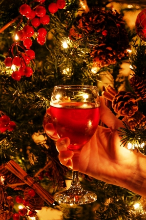 A hand holding a glass of wine in front of a Christmas tree. Stock Photo