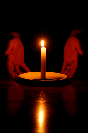 Married mans hands on either side of the soft glow of a lit candle.
