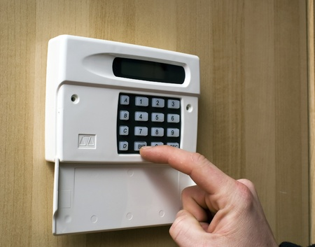 intruder: Image of a hand setting a burgler alarm
