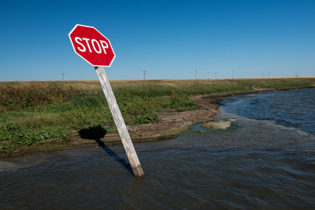 washed out: Stop sign at the corner of a flooded road.