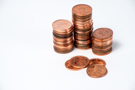 copper coin: Obsolete Canadian pennies stacked up on a white background.