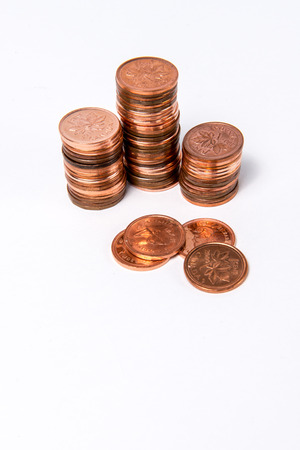 canadian currency: Obsolete Canadian pennies stacked up on a white background.