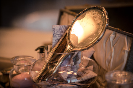 An ladies antique mirror reflects soft warm light from her vanity Stock Photo