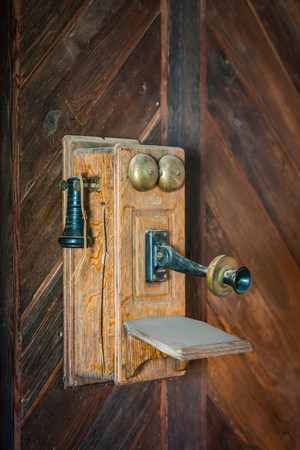 A vintage antique wooden telephone on a wall. Banque d'images - 123959764