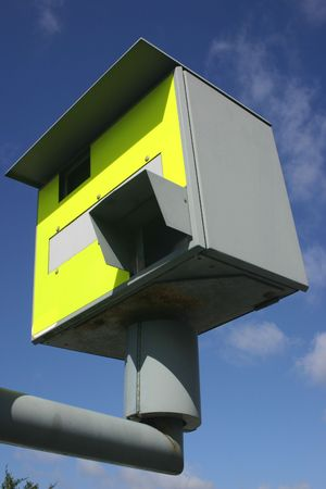 A British road traffic speed camera and a blue sky. photo