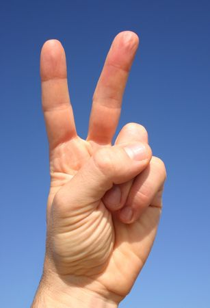 man's thumb: The Victory  Peace hand gesture and a blue sky