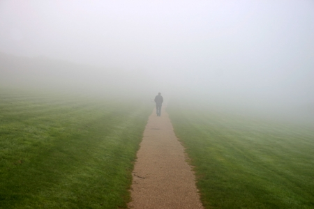 eerie: A man walking in to the mist Stock Photo