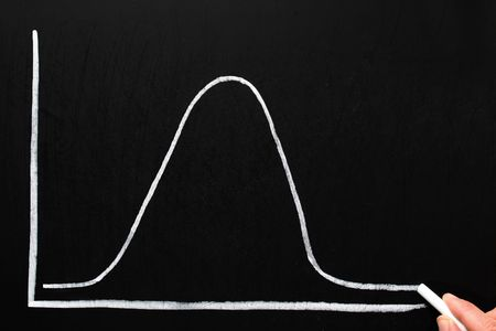 distribution: Drawing a normal distribution bell curve on a chalkboard. Stock Photo