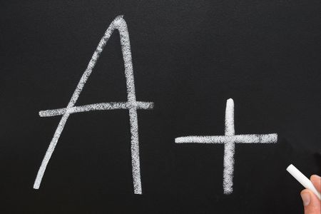test passed: A teacher writing A+ on a blackboard. Stock Photo