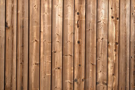 treated board: A dark stained wooden fence.