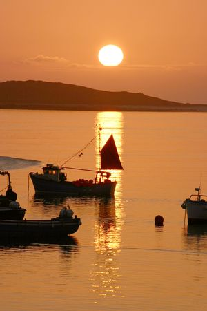 scilly: The sun setting in the Isles of Scilly Cornwall UK