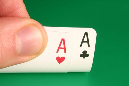 Looking at pocket aces during a poker game. Stock Photo