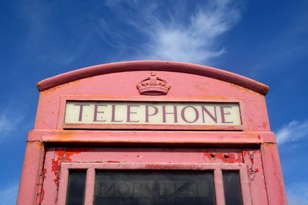 Old faded red British telephone box. photo