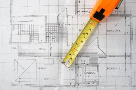 A measuring tape on top of house plans.