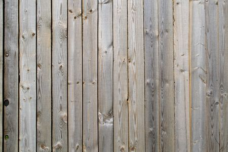 Close up of gray wooden fence panels.