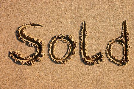 scraped: Sold written on a beach.