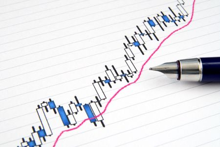 candlestick: A Japanese candlestick stock chart with shallow focus and a fountain pen. Stock Photo