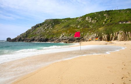 porthcurno: Waves breaking on the shore and swimming flags on Porthcurno beach.