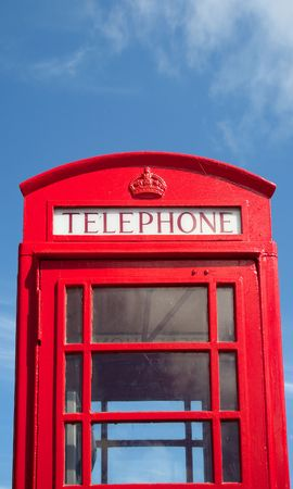 An old British red telephone box and a blue sky. photo