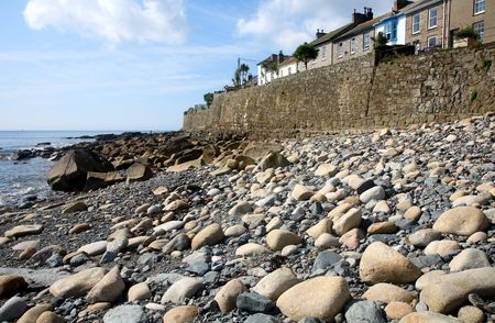 mousehole: Large boulders on the beach and the sea wall, Mousehole, Cornwall, UK. Stock Photo