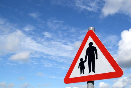 Pedestrians in road sign and a big blue sky.