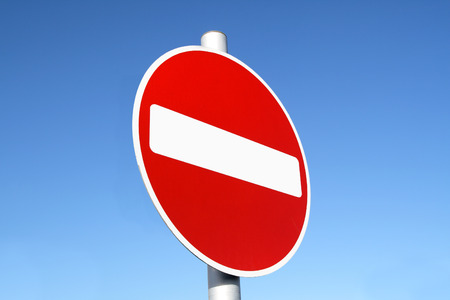 no lines: Red and white british no entry road sign with a blue sky. Stock Photo