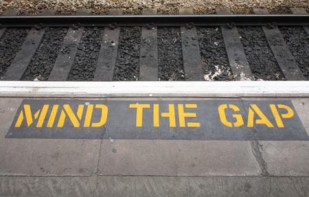 Mind the gap sign on a British railway platform. Stock Photo
