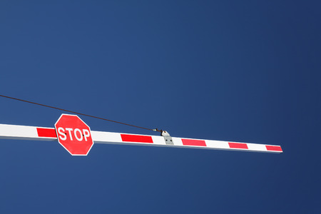 hindrance: A red stop sign on a barrier and a big blue sky.