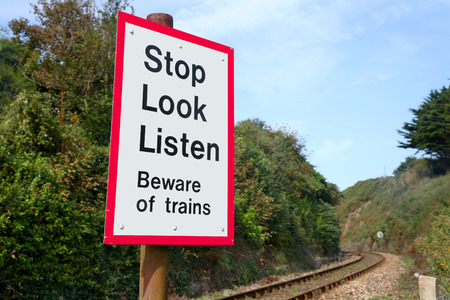 Beware of trains sign on a railway crossing. photo