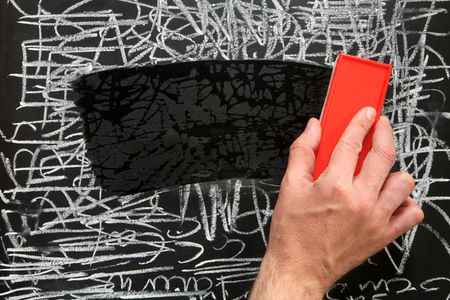 duster: Cleaning a blackboard with a red chalk duster. Stock Photo