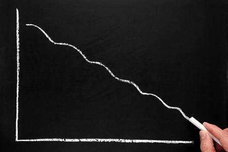 Drawing a declining profit chart on a blackboard. photo