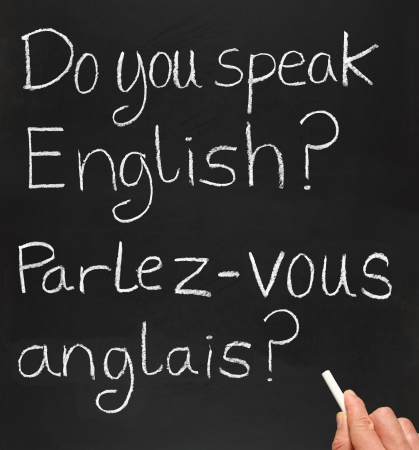 A teacher writing do you speak english in French. Stock Photo