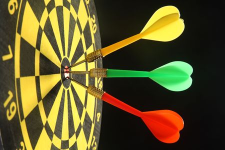 Three colourful darts in the bullseye. Stock Photo - 1833332