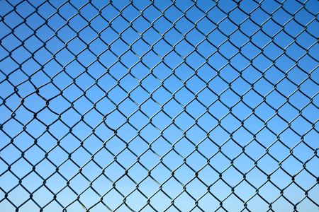 chain link: Chain link fence and a blue sky. Stock Photo