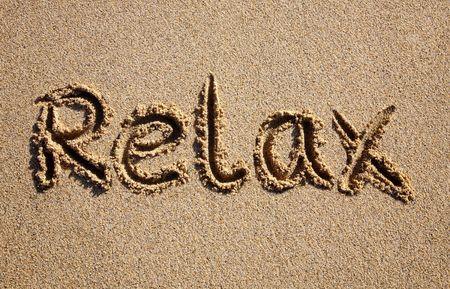 Relax, written on a sandy beach. Stock Photo