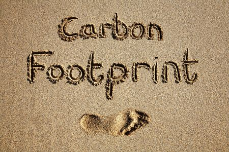 dioxido de carbono: Huella del carb�n escrita en arena en una playa.